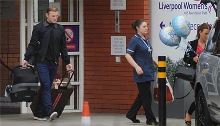 Rooney khệ nệ tay xách vali quần áo cho vợ, tay xách nôi em bé, đi sau bà xã ra xe.
