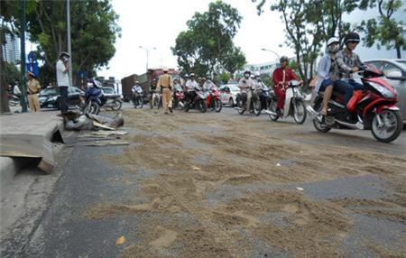 Lực lượng CSGT dùng cát để lấp vệt dầu và điều tiết giao thông