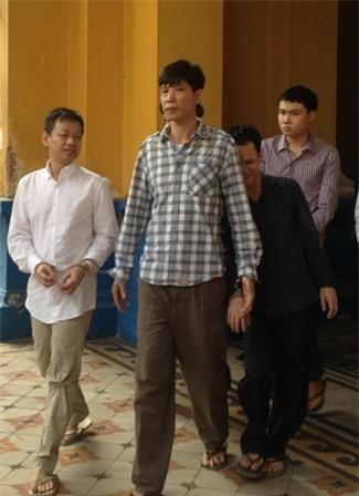 Mai Phước Hoàng mặc áo đen, nấp sau lưng