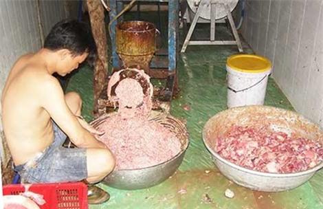 Ở trần ngồi xay thịt với máy xay rỉ sét