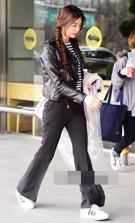 Nữ diễn viên Uhm Hyun Kyung lựa chọn quần ống loe chất liệu vải đi cùng áo da lửng. Giày sneaker trắng, sọc đen tô điểm cho phong cách ấn tượng của người đẹp.