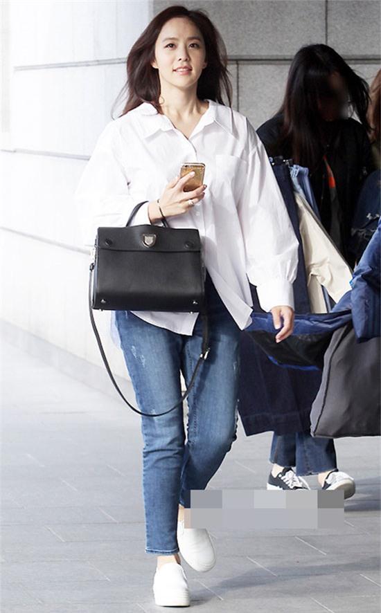 Áo sơ mi trắng là món đồ không thể thiếu trong tủ đồ của bất cứ cô nàng nào. Park Ji Yoon diện quần jeans xanh, áo sơ mi trắng dáng thụng và túi xách đen, giày sneaker rất tinh tế.