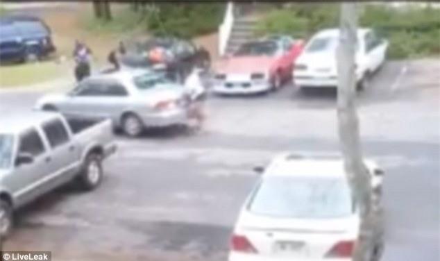 Cô gái chạy lại phía sau xe để nhặt vật nặng định chọi xe bạn trai một cú nữa...