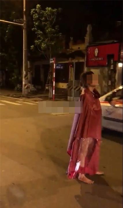 Người đàn bà mặc áo mưa đi giữa phố Hà Nội gây chú ý - Ảnh 1.