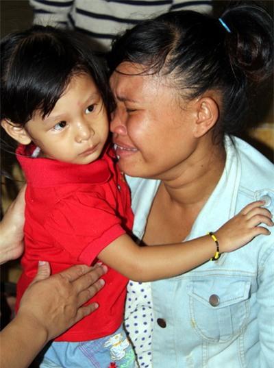 Chị Liên bật khóc ôm đứa con 3 năm nay mình nuôi dưỡng trước khi trao trả lại cho vợ chồng anh Khiên. Ảnh: Phước Tuấn