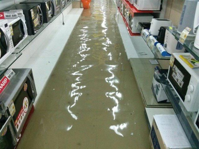 Mưa lớn ở Sài Gòn, nước tràn vào siêu thị điện máy - Ảnh 1.