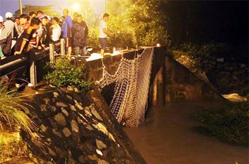Lực lượng chức năng đang giăng lưới ở miệng cống suối Nhum, đoạn chảy qua làng Đại học Quốc gia TP HCM. Ảnh: Phước Tuấn