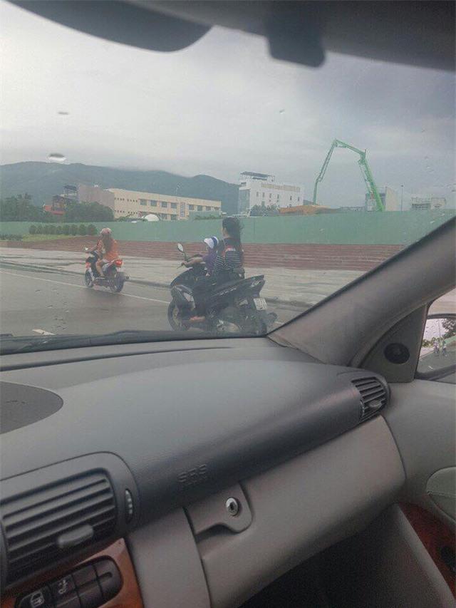 Thót tim cảnh bé trai lái xe máy chở theo một cô gái không đội mũ bảo hiểm trên đường - Ảnh 1.