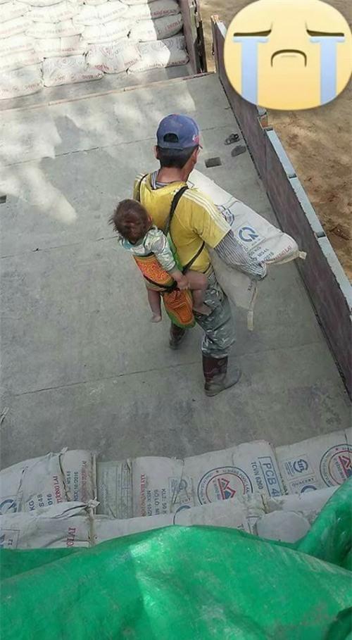 Người bố vừa địu con, vừa vác xi măng kiếm sống.