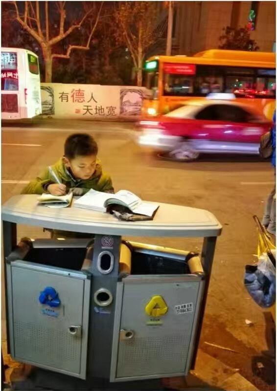 Hình ảnh cậu bé chăm chỉ học bài trên thùng rác cạnh xe khoai lang nướng của mẹ gây xúc động mạnh - Ảnh 2.