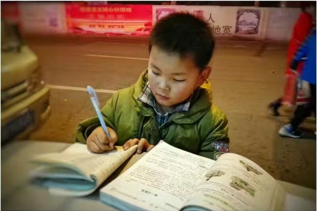 Hình ảnh cậu bé chăm chỉ học bài trên thùng rác cạnh xe khoai lang nướng của mẹ gây xúc động mạnh - Ảnh 3.