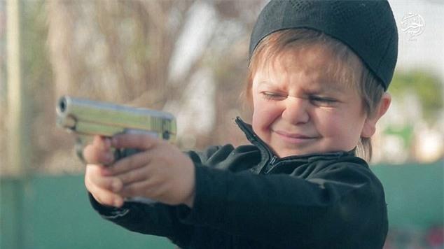 Rùng mình khoảnh khắc đứa trẻ vài tuổi dùng súng hạ sát một tù nhân IS - Ảnh 1.