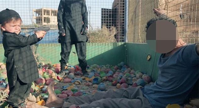 Rùng mình khoảnh khắc đứa trẻ vài tuổi dùng súng hạ sát một tù nhân IS - Ảnh 2.