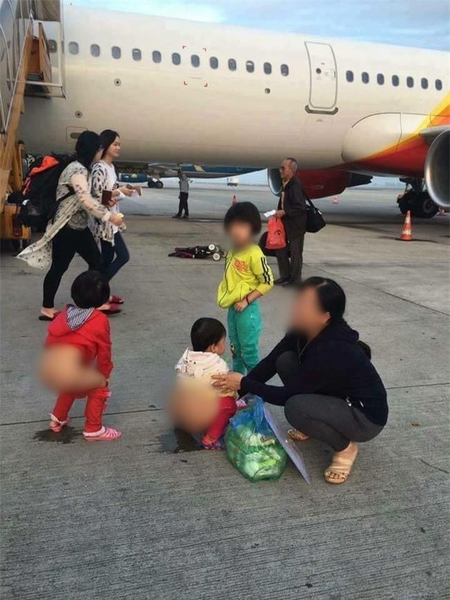 Người mẹ hồn nhiên cho 2 bé gái đi vệ sinh ngay giữa đường băng máy bay - Ảnh 1.