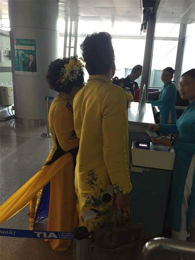 Vợ MC Thanh Bạch diện áo dài như đuôi công lên máy bay khiến nhiều hành khách choáng - Ảnh 1.