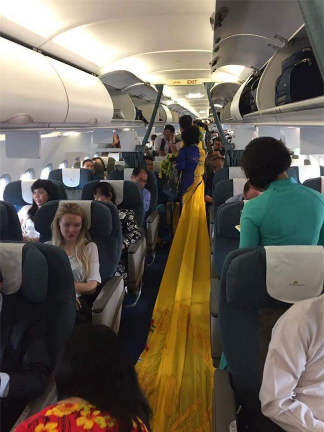 Vợ MC Thanh Bạch diện áo dài như đuôi công lên máy bay khiến nhiều hành khách choáng - Ảnh 4.