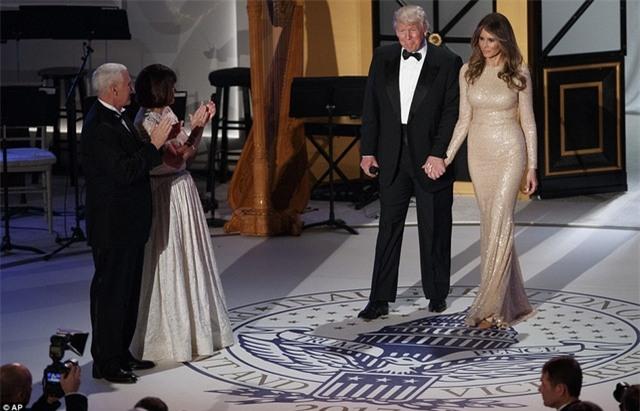 Phu nhân của ông Trump, bà Melania, với tông màu trang điểm nhẹ, xuất hiện trong bữa tiệc với một chiếc đầm đuôi cá óng ánh của nhà thiết kế nổi tiếng Reem Arca thay vì chiếc đầm của nhà thiết kế Ralph Lauren như đồn đoán trước đó. Bà sánh vai bên chồng bước ra sân khấu giữa những tràng pháo tay của hơn 1.000 khách mời. (Ảnh: AP)