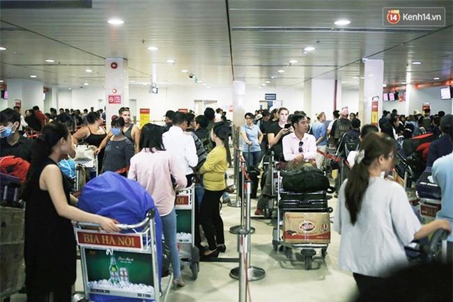 Chùm ảnh: Cận Tết, biển người vật vã hàng tiếng đồng hồ chờ check in ở sân bay Tân Sơn Nhất - Ảnh 2.