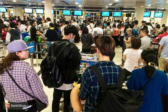 Chùm ảnh: Cận Tết, biển người vật vã hàng tiếng đồng hồ chờ check in ở sân bay Tân Sơn Nhất - Ảnh 3.