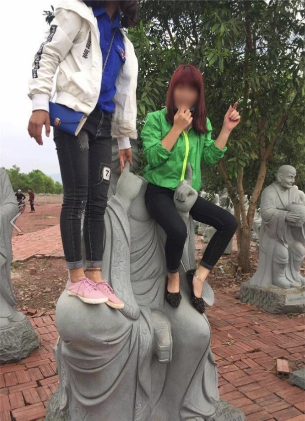 Hai cô gái trẻ ngồi lên tượng phật để tạo dáng chụp ảnh khiến nhiều người phẫn nộ - Ảnh 1.