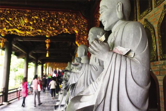 Hiện tượng nhét tiền vào tay tượng vẫn tồn tại ở nhiều đền, chùa. Ảnh: Chí Cường