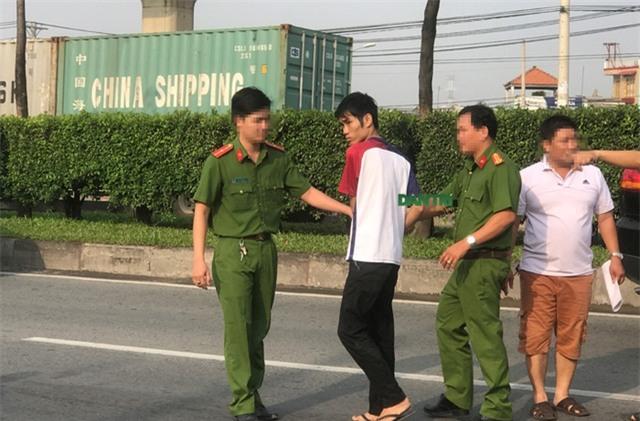 Lực lượng Công an dẫn giải nghi can Duy (áo thun trắng đỏ) ra lại XLHN để thực nghiệm hiện trường.