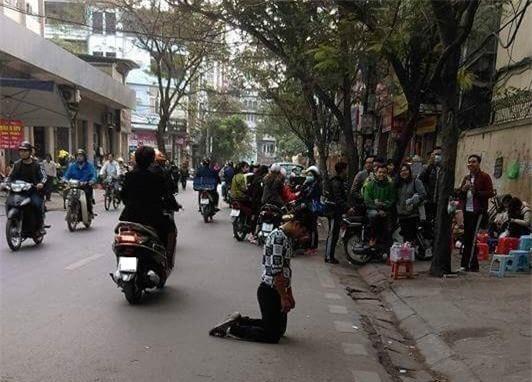 Chang trai quy goi xin loi ban gai tren duong di le chua hinh anh 2
