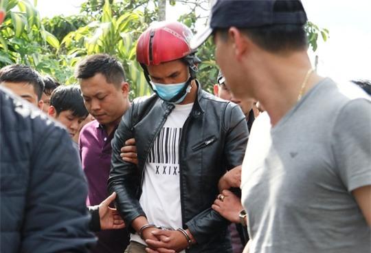 Lực lượng chức năng dẫn giải hung thủ Nguyễn Thành Đức đến nơi khai quật tử thi nạn nhân.