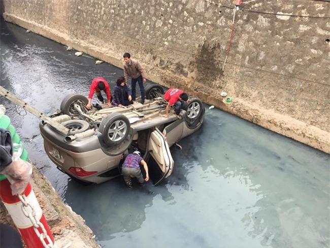 Hà Nội: Ô tô lao xuống mương nước rồi lật ngửa, người dân cạy cửa cứu người phụ nữ mắc kẹt ra ngoài - Ảnh 1.