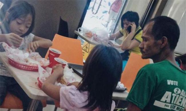 Hình ảnh người cha khắc khổ lặng lẽ nhìn 2 con gái nhỏ say sưa ăn gà rán khiến nhiều người rơi nước mắt - Ảnh 1.