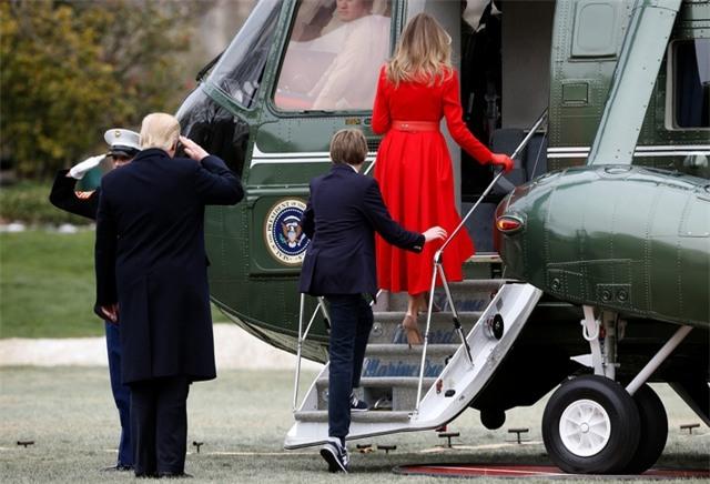 Sau khi rời Nhà Trắng, gia đình ông Trump lên trực thăng Marine One, máy bay đặc biệt được thiết kế riêng để phục vụ cho nhu cầu đi lại trong phạm vi ngắn của tổng thống Mỹ, tới căn cứ không quân Andrews ở bang Maryland. Trong ảnh: Tổng thống Trump chào một sĩ quan quân đội trước khi bước lên trực thăng Marine One.