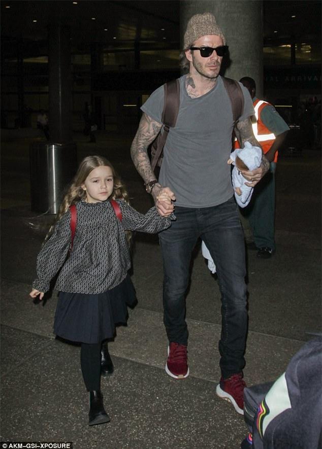 Harper nắm chặt tay bố khi xuất hiện ở sân bay cùng 3 anh trai - Ảnh 1.