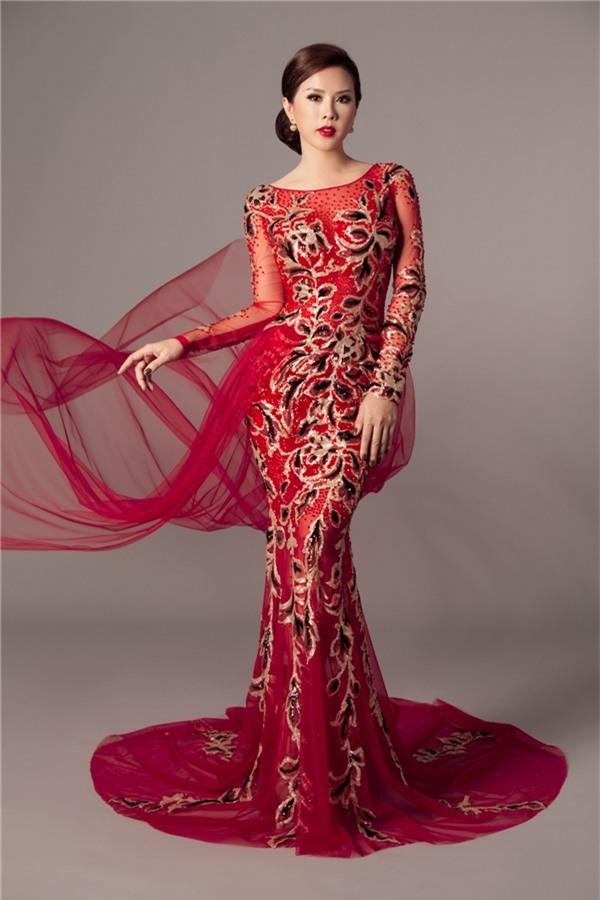 Sắc đỏ quyền lực kết hợp tông vàng đồng giúp tổng thể bắt mắt. Phần voan lụa mềm mại, mỏng manh bên ngoài giúp thiết kế thêm lạ mắt trên nền phom váy đuôi cá kinh điển.