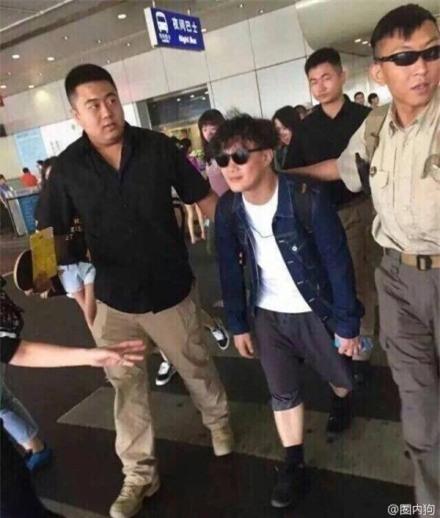 Trần Dịch Tấn quá là bé nhỏ so với các chàng vệ sĩ ngoài sân bay.