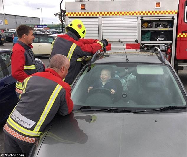 Bé trai 14 tháng tuổi cười nắc nẻ khi 5 nhân viên cứu hỏa ra sức tìm cách cứu cậu bé ra khỏi ô tô - Ảnh 1.