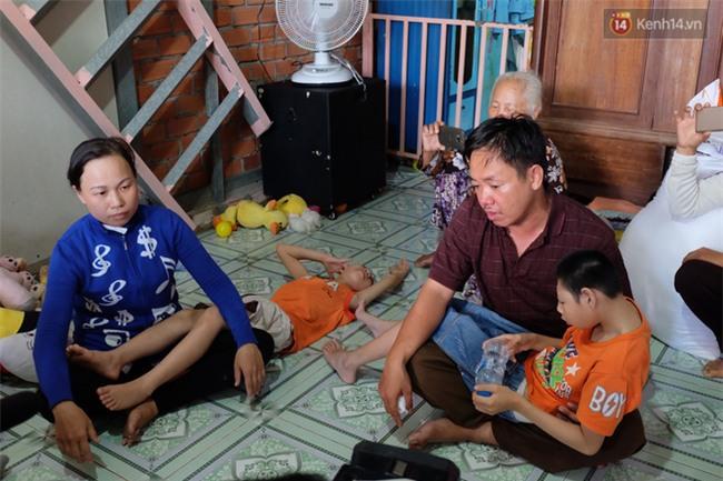 Người cha có 2 con bại não bất ngờ phát gạo từ thiện cho người dân nghèo ở xung quanh - Ảnh 1.