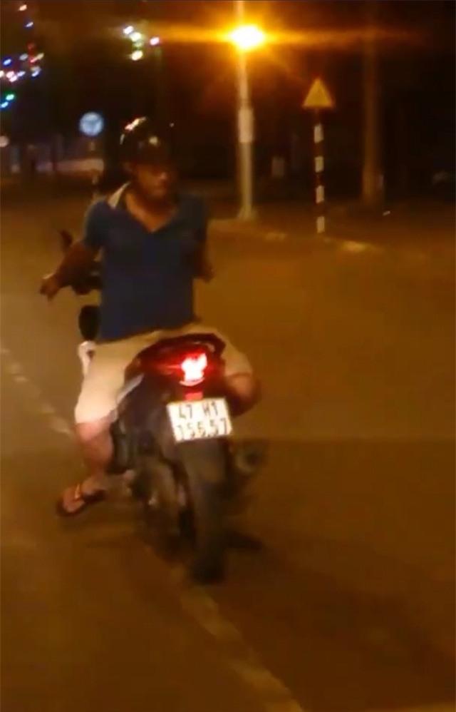 Nam thanh niên ngồi quay lung điều khiển xe máy (ảnh cắt từ clip)