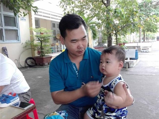 Chồng bế con 9 tháng tuổi theo vợ đi thi - ảnh 1