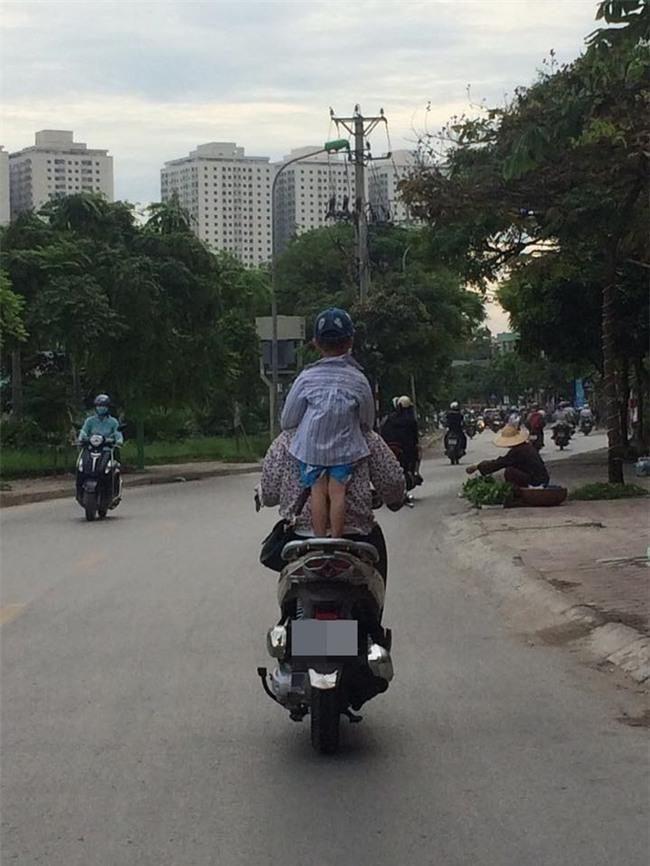 Hình ảnh nguy hiểm trên phố Hà Nội và ánh mắt của người mẹ khiến dân mạng bức xúc - Ảnh 1.