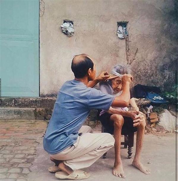 Bức ảnh người con trai cắt tóc cho mẹ già lay động trái tim cộng đồng mạng - Ảnh 1.