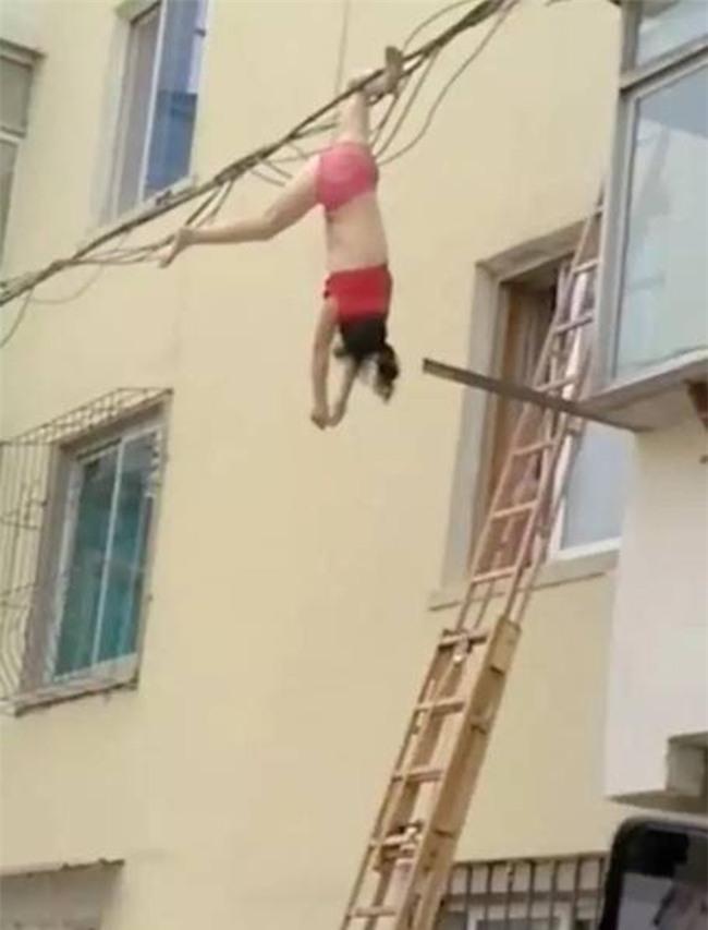 Mặc nội y lau cửa sổ, thế nào lại bị rơi xuống rồi mắc chân vào dây điện, người phụ nữ ngất giữa không trung - Ảnh 2.