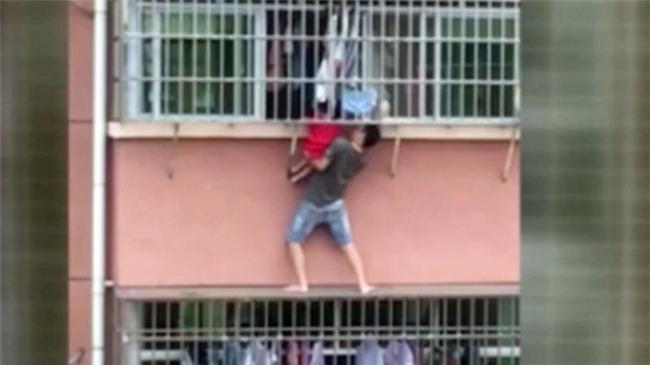 Mạo hiểm cứu bé trai treo lủng lẳng ở cửa sổ nhà cao tầng - Ảnh 1.