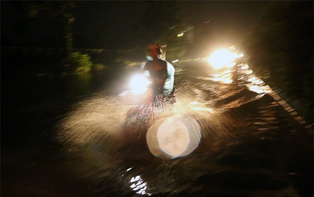 Nhiều người đi xe máy liều mình lao qua những đoạn ngập trên đường gom Đại lộ Thăng Long.