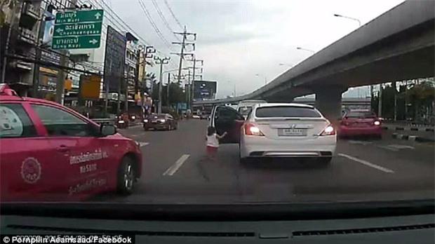 Bé gái đột ngột ngã lăn từ trên ô tô đang chuyển bánh xuống đường phố đông đúc - Ảnh 2.