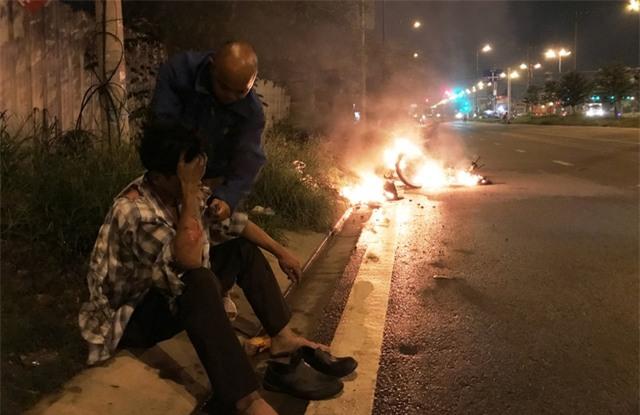 Người đàn ông (ngồi) được tài xế xe đầu kéo container giải cứu bên chiếc xe máy bao trùm trong biển lửa.