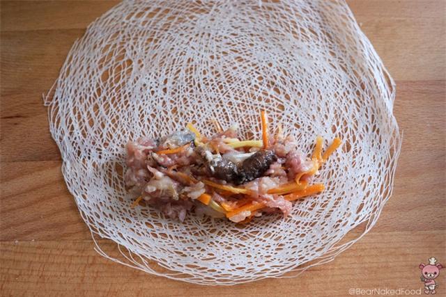 Khi gói nem, cho 2 thìa nhân vào rìa ngoài cùng của bánh đa nem và cuộn chặt tới phần giữa bánh.
