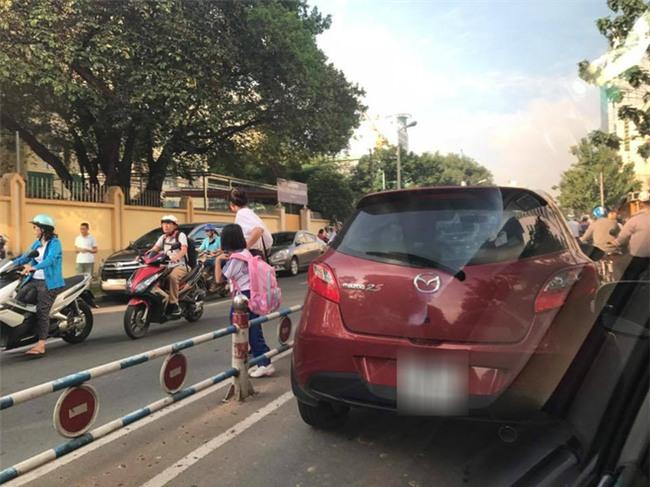 Dừng giữa đường, mẹ ngang nhiên mở cửa xe dẫn con vào trường học gây bức xúc - Ảnh 1.