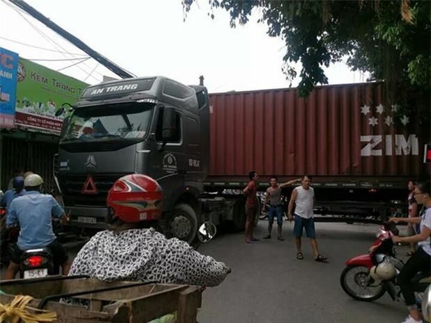 Bất chấp nguy hiểm, người dân thi nhau chui gầm container chắn ngang giữa đường để lưu thông - Ảnh 1.