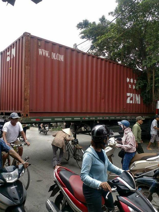 Bất chấp nguy hiểm, người dân thi nhau chui gầm container chắn ngang giữa đường để lưu thông - Ảnh 4.