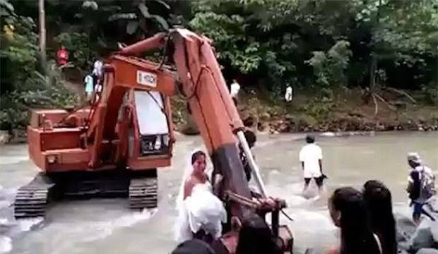 Video: Nước dâng cao chắn lối, cặp uyên ương dùng máy xúc vượt suối về nhà trong đám cưới - Ảnh 2.